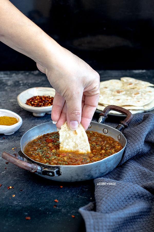 chapati e dahl indiano con mano